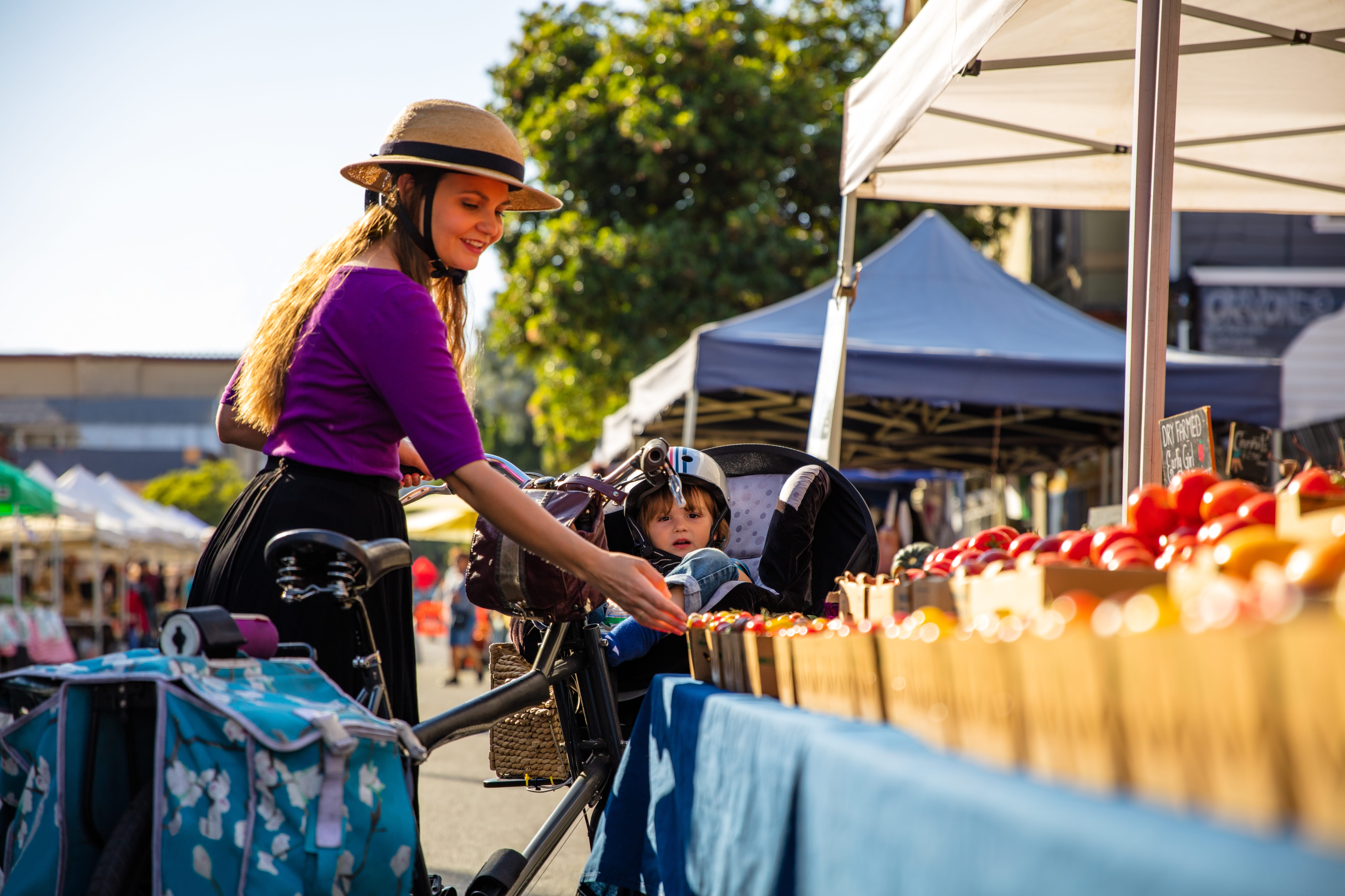 woman in purple shirt and trendy hat shopping at san francisco farmers market
