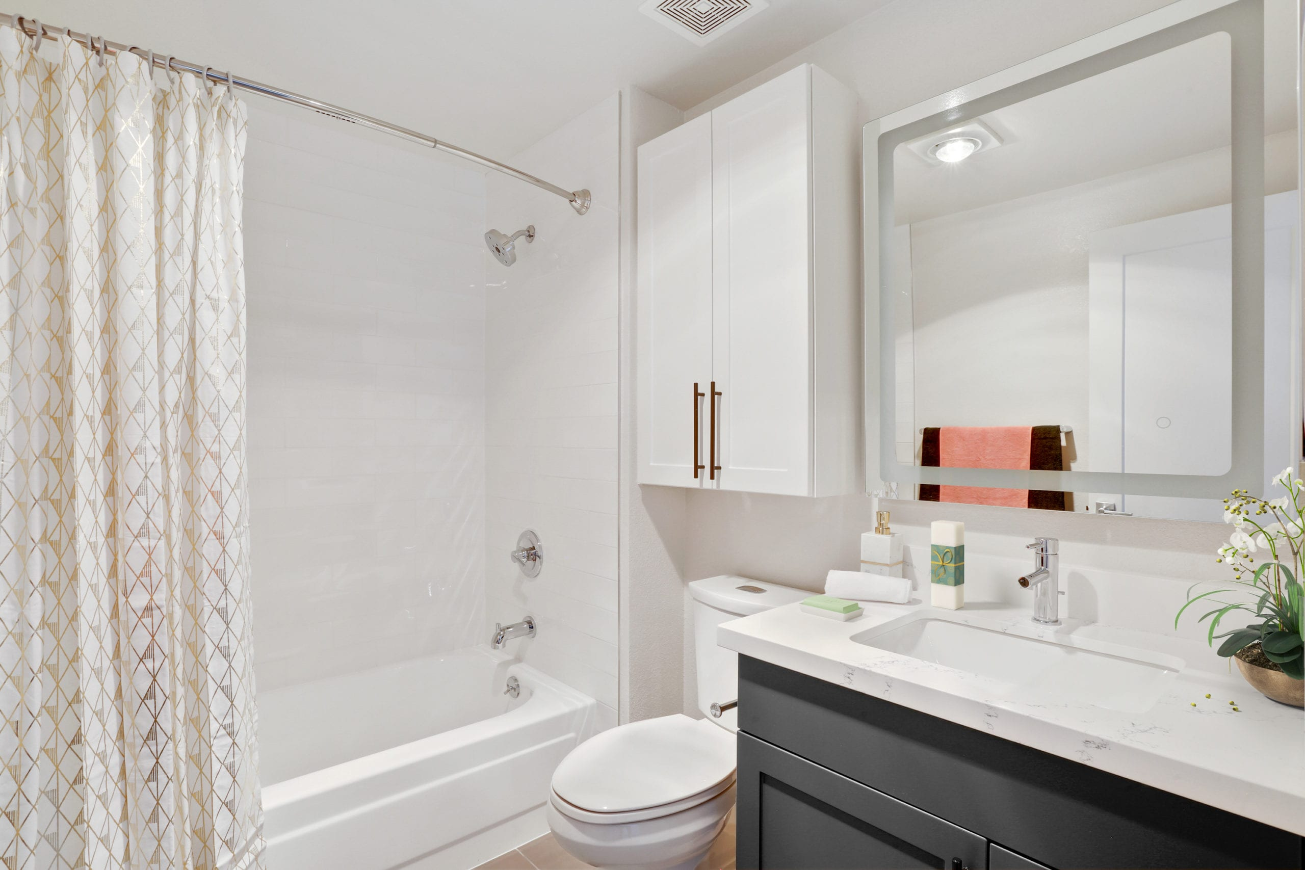 bathroom with shower tub and gray vanity